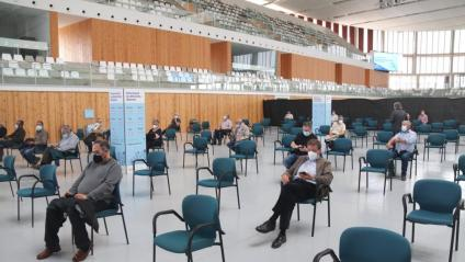 Diverses persones esperen alguns minuts després de vacunar-se, en un espai habilitat al Palau d'Esports de Tarragona