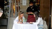 Un cambrer atén una taula d'una terrassa, al centre de Barcelona