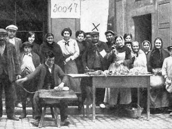 L'expenedor dels bitllets de la grossa de Nadal amb un grup d'afortunats de la loteria, l'any 1914 a Ripoll. Al fons, un cartell amb el número premiat
