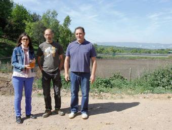 Noemí Cuenca, amb un pot amb l'aigua ja depurada; Marc Garriga, i Josep Masramon, propietari d'El Bruguer, davant la bassa amb tot el purí que es tran Sagi Serra