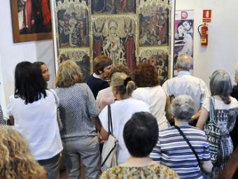Un grup d'assistents observen de prop el retaule Ramon Ferrandis