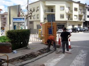Uns operaris treballen per eliminar barreres arquitectòniques en un carrer de Solsona.