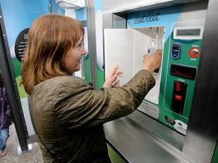 Una persona comprant llet de la màquina expenedora.  M.LL
