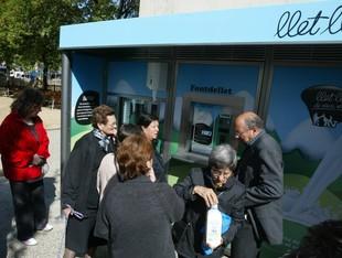 La màquina expenedora de llet situada a l'exterior del mercat de Salt, en ple funcionament, ahir al matí.  JOAN SABATER