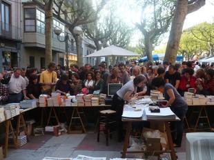 A l'esquerra, una parada de llibres al Firal. A la dreta, la lectura pública del Servei de Català i l'espai de Ràdio Olot.  J.C