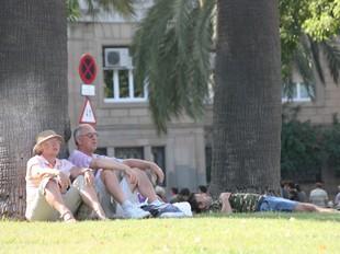 Dues persones assegudes en un parc de Barcelona.  LUIS ALBERTO