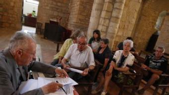 Mossèn Viñas, escoltant les queixes dels veïns, amb l'alcalde al fons.  LLUÍS SERRAT