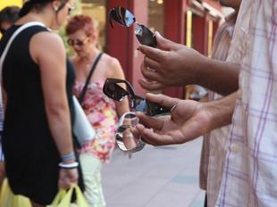 Uns venedors oferint unes ulleres de sol al nucli fronterer d'El Pertús.  LLUÍS SERRAT