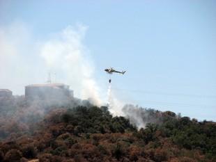 Un helicòpter sobrevola una zona afectada pel foc, ahir.  ACN