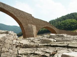 A l'esquerra, el pont de Querós, que queda a la vista quan hi ha sequera. A la dreta, imatges del poble i la vall abans de quedar negats pel pantà i en el moment de la inundació.  LLUÍS SERRAT / ARXIU HISTÒRIC COMARCAL DE LA SELVA
