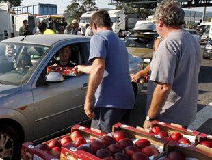 Agricultors nord-catalans repartint fruita al peatge d'El Voló en una acció de protesta a final de juliol.  EFE
