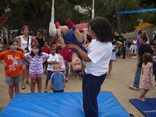 Un nen fa una tombarella en un trapezi durant el taller de circa la plaça de Catalunya de Terrassa.  M.A.L