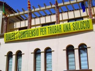 L'alcalde ha penjat una pancarta a l'ajuntament demanant diàleg per solucionar el conflicte.