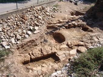 Una imatge dels paraments de les dues muralles, una sitja i un tram del camí de ronda de la primera muralla, a la plaça de l'església dels Sants Metges. /  D.C