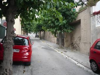 El carrer, amb arbres i cotxes aparcats sobre la vorera.  J.N