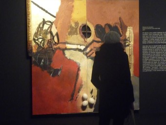 Una dona mira el «Retaule de Jerusalem» de Guinovart al Museu de Lleida.  D.M