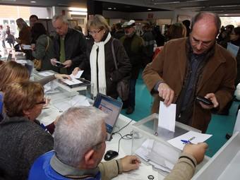 Un home, a la dreta de la imatge, diposita un vot a l'urna, el passat 13 de desembre a Sant Cugat del Vallès.  ORIOL DURAN