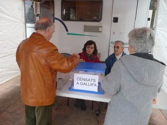 Dos ciutadans de Gallifa votant i detall de la pancarta a l'entrada del poble.  M.C.B