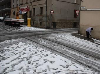 Un veí treu la neu d'un carrer d'Igualada.  ACN