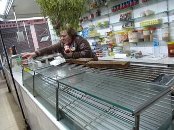 La comerciant Mari Carme Calduch retirada els últims pots de conserva del taulell abans de plegar.  A. ESTALLO
