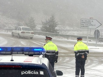 Els Mossos d'Esquadra controlant el trànsit en un dels accessos a l'eix transversal, que es va haver de tallar per la neu.  ROBIN TOWNSEND / EFE