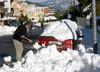 Un veí d'Horta de Sant Joan, netejant el cotxe de neu amb la pala EFE