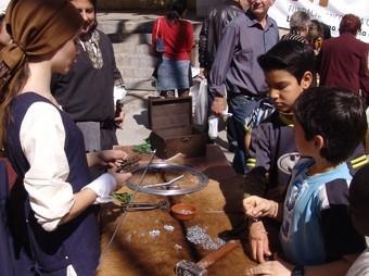 Alguns joves observen la tècnica del filferro en una parada del mercat.