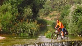 Un cicloturista travessant el riu Algars.  ROSA DÍAZ