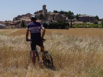El ciclista observa de lluny la imatge retallada al cel del nucli urbà del Vilosell, format al voltant de l'església parroquial de Santa Maria.  XANASCAT