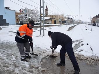 Dos homes traient la neu a pales al pas a nivell de l'estació de Tàrrega.  DAVID MARÍN
