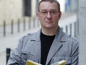 L'agent Santi Fornell amb el seu llibre Bufi aquí! , en un carrer de Barcelona.  ANDREU PUIG