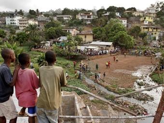 Grup de xiquets i xiquetes africans que juguen al futbol en un descampat. /  ARXIU