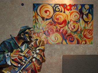 El saxofonista i un quadre de tema floral, a la mostra de l'obra de Morales, als Jardins de la Mercè. /  P.M