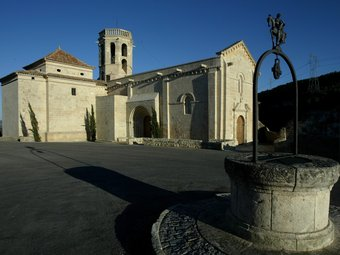 El pou que hi ha al centre de la llotja natural i, al fons, l'església romànica de Santa Maria.  JUANMA RAMOS