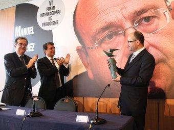 Ramon Besa sosté el guardó, aplaudit per Martí i Laporta, ahir al Camp Nou.  EL 9