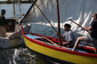A l'esquerra, la barca amb motor d'Henri Conte talla el pas de la barca catalana amb els seus ocupants, que intenten apartar-la amb perxes.