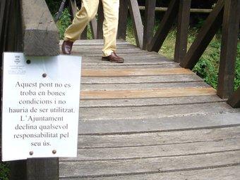 Un senyor travessa un pont de fusta en males condicions a Santa Pau. Tura Soler