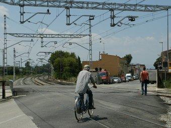 Un ciclista i un vianant travessen el pas a nivell de Flaçà que encara travessa el municipi. MIQUEL RUIZ