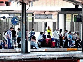 Passatgers esperen un tren amb quasi una hora de retard a les andanes de l'estació de Girona ahir a migdia. JORDI SOLER