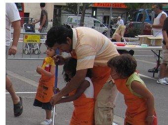 Un pare i unes nenes fent com qui frega el terra en la gimcana de dissabte. EL PUNT