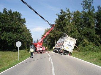 Una grua aixeca el camió tombat TURA SOLER