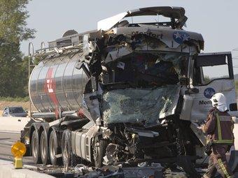 La part frontal del camió cisterna que va quedar completament destrossada, amb un dels bombers que treballaven en el lloc de l'accident. LLUÍS SERRAT