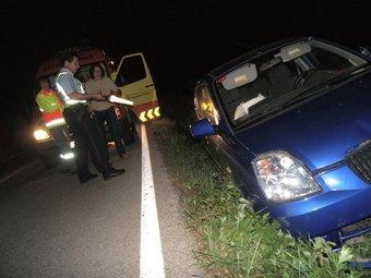El cotxe i la conductora al costat d'un mosso que inspecciona el lloc. JOAN GUIRADO / GARROTXA.INFO