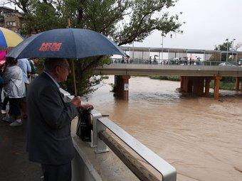 Un home observa el riu Anoia desbordat al seu pas per Martorell. ACN