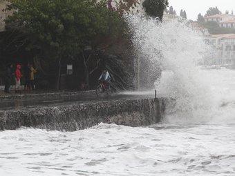 Una onada petant contra el front de mar de Cadaqués, amb vianants mirant el temporal i un ciclista esquivant l'aigua. ANDREU PUIG