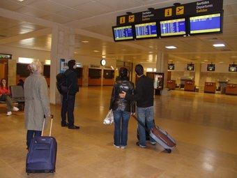Viatgers ahir al matí observant les pantalles d'informació a la terminal de sortides de l'aeroport de Girona, on Ryanair va cancel·lar diversos vols. O.M
