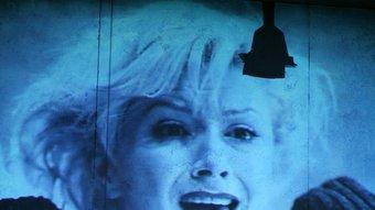 Sandra Korzeniak mira la seva pròpia imatge projectada a l'escenografia, en un moment de l'obra K. PALETKO