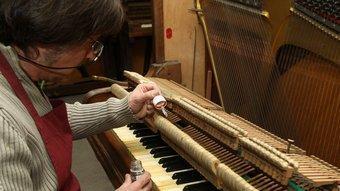 Un expert condiciona un piano amb molts anys d'història.  ARXIU