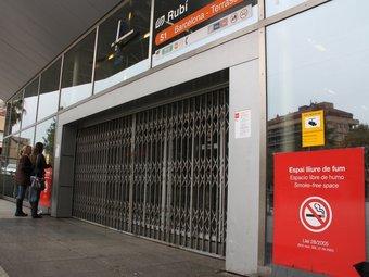 Dues usuàries llegeixen un cartell informatiu enganxat a la façana de l'estació tancada per la vaga ACN