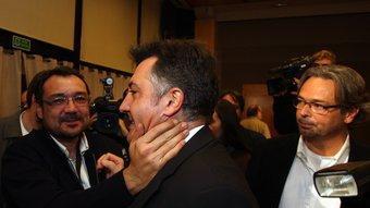 El president d'ERC al País Valencià, Agustí Cerdà, consola Puigcercós després de conèixer els resultats, sota la mitrada de Benach. ORIOL DURAN